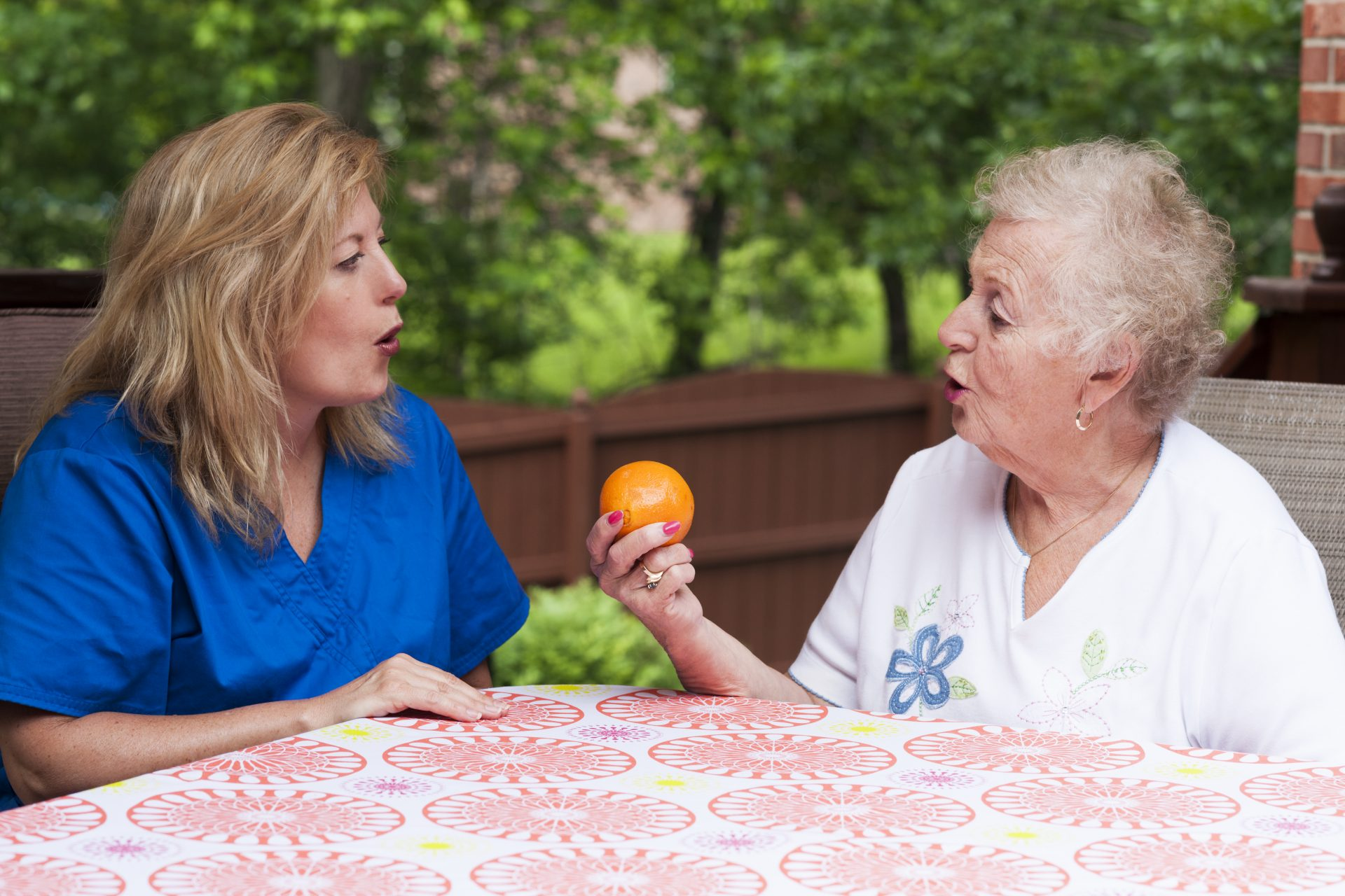 Speech pathologist with female stroke patient outdoors during a home health therapy session modeling the production of a consonant during speech training for apraxia